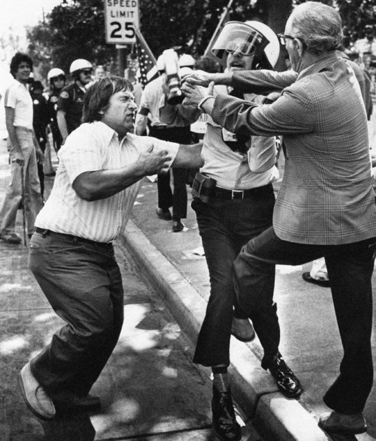 A Nazi demonstrator fights with anti-Nazi protestors during a demonstration by the National Socialist White Workers Party at St. James Park in San Jose, Calif., October 8, 1977. Eight uniformed Nazis dodged eggs, tomatoes, sticks and fists, as an angry crowd of 2,000 made pandemonium of the white-power demonstration. (Photo by Paul C. Strong/AP Photo)