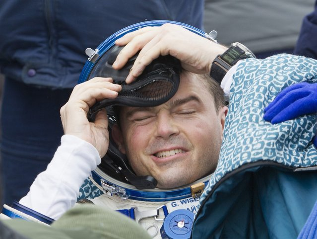 International Space Station (ISS) crew member Reid Wiseman of the U.S. takes off his helmet after landing in a remote area near the town of Arkalyk in northern Kazakhstan November 10, 2014. (Photo by Shamil Zhumatov/Reuters)