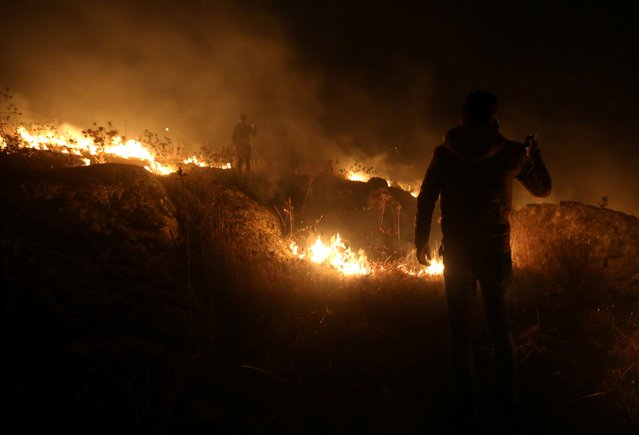 A man uses his phone near a fire in Houla village near the Lebanese-Israeli border, in southern Lebanon, August 25, 2020. (Photo by Aziz Taher/Reuters)