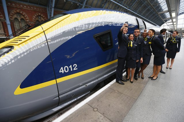 Eurostar employees pose for a selfie next to their new Siemens e320 train at St Pancras station in central London, November 13, 2014. Eurostar, the company that runs passenger trains through the Channel tunnel between London and Paris, said it would buy seven additional e320 trains from Siemens for about 300 million pounds ($473 million). The company placed an order for 10 new trains in 2010, the first of which is due to enter commercial service next year, enabling the company to add new routes. (Photo by Andrew Winning/Reuters)
