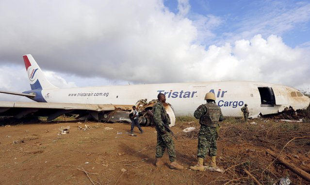 Ugandan soldiers serving in the African Union Mission in Somalia (AMISOM) secure the site where a Tristar Air Airbus A300-200F cargo plane crash-landed in Arbiska outside Somalia's capital Mogadishu, October 13, 2015. (Photo by Feisal Omar/Reuters)