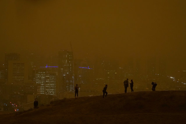 People look toward the skyline obscured by wildfire smoke during daytime from Kite Hill Open Space in San Francisco, Wednesday, September 9, 2020. (Photo by Jeff Chiu/AP Photo)
