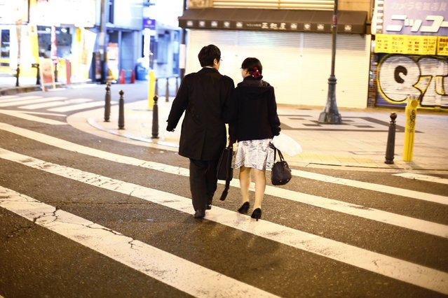 A couple cross a street in the amusement district of Osaka, western Japan November 19, 2014. (Photo by Thomas Peter/Reuters)