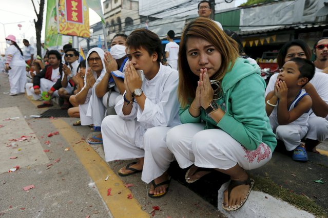 People pray on the street as they watch devotees of the Chinese Ban Tha Rue shrine procession celebrating the annual vegetarian festival in Phuket, Thailand, October 17, 2015. (Photo by Jorge Silva/Reuters)