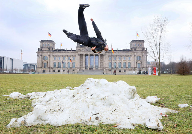 Hadi from Denmark jumps over one of the last heaps of snow during a stop of his tourist group in front of the Reichstag Building in Berlin,on February 28, 2013. (Photo by Stephanie Pilick/AFP Photo)