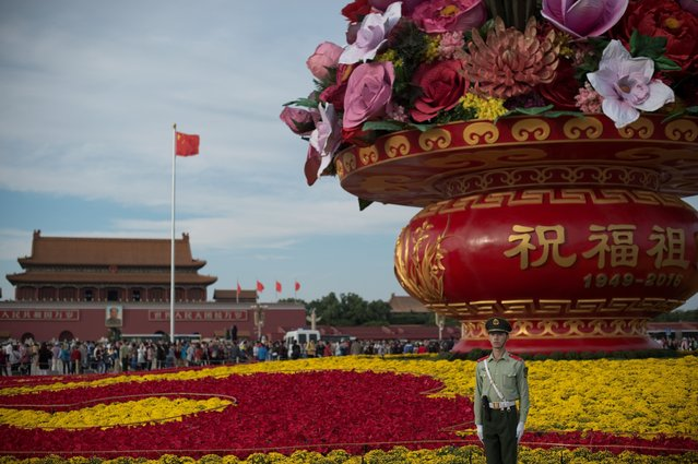 A paramilitary soldier (bottom R) stands in front of a giant flower bouquet that stands on Tiananmen Square to commemorate the upcoming Chinese National Day in Beijing on September 27, 2016. The Chinese National Day is celebrated annually on October 1 to commemorate the founding of the People's Republic of China. (Photo by Nicolas Asfouri/AFP Photo)