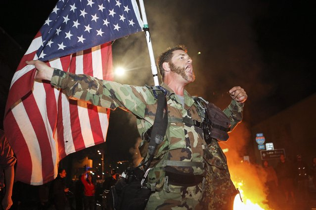 James Cartmill, of Veterans for Peace, holds an American flag upside down, to indicate distress, during a demonstration in Oakland, California November 24, 2014, following the grand jury decision in the shooting of Michael Brown in Ferguson, Missouri. (Photo by Elijah Nouvelage/Reuters)