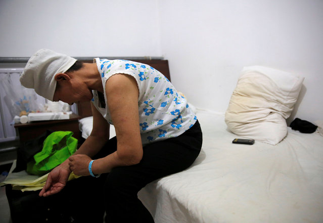 Huang sits on a bed in her room at the accommodation where patients and their family members stay while seeking medical treatment in Beijing, China, June 22, 2016. (Photo by Kim Kyung-Hoon/Reuters)