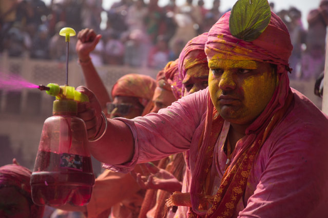 Indians celebrate Holi, the spring festival of colours, during a traditional gathering at Nandbaba temple in Nandgaon village of Mathura district in Uttar Pradesh, India on February 25, 2018. Holi is observed in India at the end of the winter season on the last full moon of the lunar month. (Photo by Javed Sultan/Anadolu Agency/Getty Images)