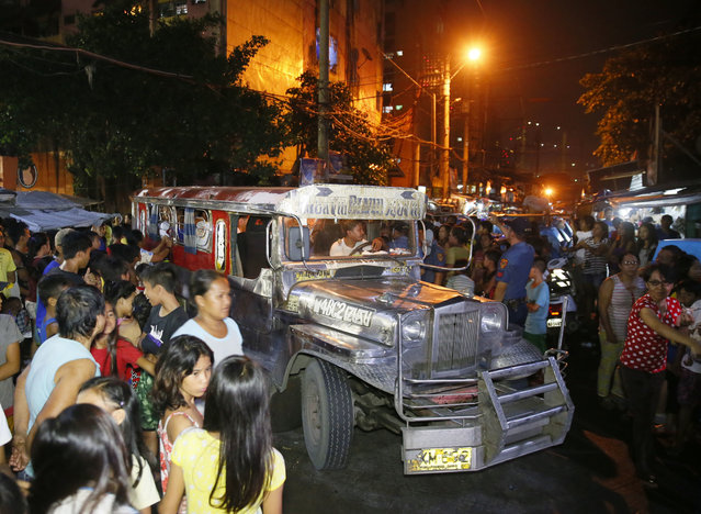 "Residents and relatives gather around a vehicle wherein rounded up males prepare to be transported to a police station in the continuing ""War on Drugs"" campaign of President Rodrigo Duterte at slum community of Tondo in Manila, Philippines late Friday, September 30, 2016. (Photo by Bullit Marquez/AP Photo)"