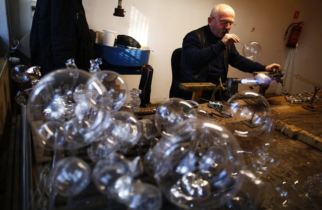 A worker blows a glass bauble at the Silverado manufacture of hand-blown Christmas ornaments in town of Jozefow outside Warsaw December 2, 2014. (Photo by Kacper Pempel/Reuters)