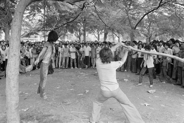 In this October 6, 1976 file photo a member of a Thai political faction strikes at the lifeless body of a hanged student outside Thammasat University in Bangkok Oct. 6, 1976. (Photo by Neal Ulevich/AP Photo)