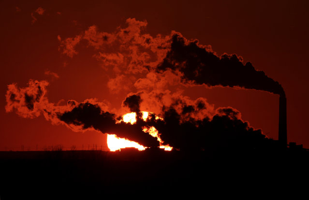 In this March 8, 2014 file photo, steam from the Jeffrey Energy Center coal-fired power plant is silhouetted against the setting sun near St. Mary's, Kan. A groundbreaking agreement struck Wednesday, November 12, 2014, by the United States and China puts the world's two worst polluters on a faster track to curbing the heat-trapping gases blamed for global warming. (Photo by Charlie Riedel/AP Photo)