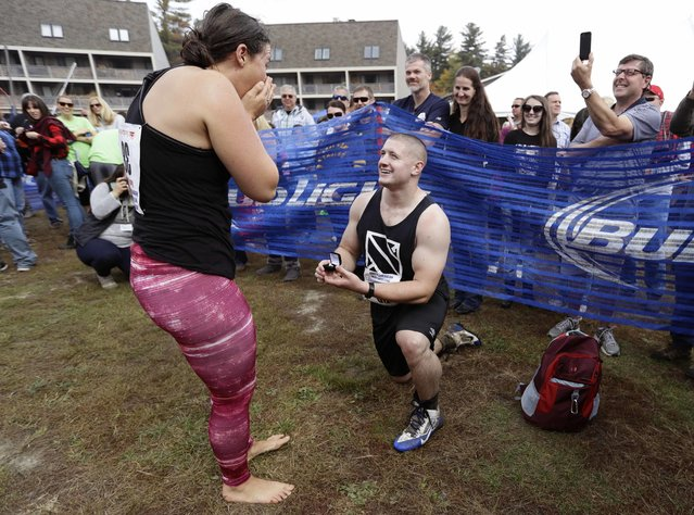 Alex Gauvin proposes to his girlfriend Casey Maynard, both of Westbrook, Maine, after completing the 278-yard obstacle course at the North American Wife Carrying Championship, Saturday, October 8, 2016, at the Sunday River Ski Resort in Newry, Maine. (Photo by Robert F. Bukaty/AP Photo)