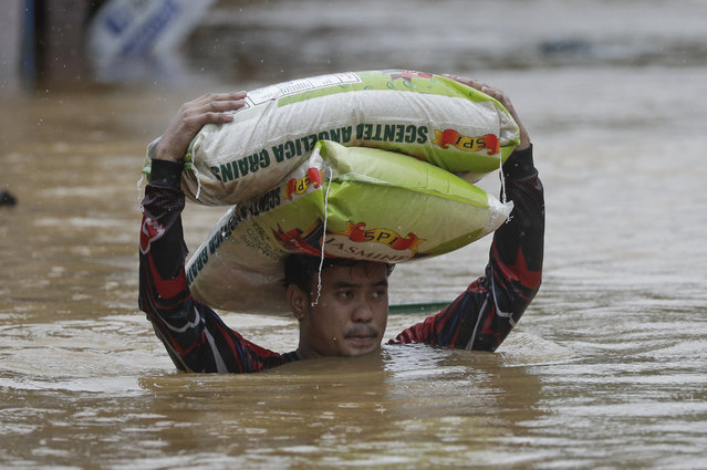A man carries sacks of rice over floodwaters as it continues to rise in Marikina, Philippines due to Typhoon Vamco on Thursday, November 12, 2020. A typhoon swelled rivers and flooded low-lying areas as it passed over the storm-battered northeast Philippines, where rescuers were deployed early Thursday to help people flee the rising waters. (Photo by Aaron Favila/AP Photo)