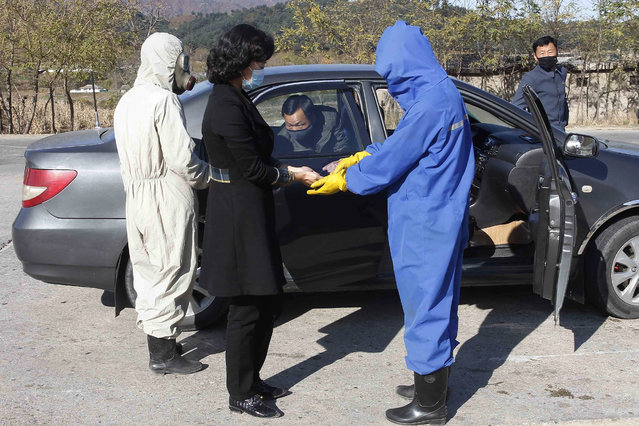 Hygienic and anti-epidemic officials disinfect and check the temperature of people coming into the city of Wonsan, Kangwon Province, North Korea DPRK, on Wednesday, October 28, 2020. (Photo by Jon Chol Jin/AP Photo)