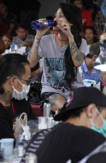 A girl drinks as she gets a tattoo on her leg during Bandung Body Art Festival at in Bandung, West Java, on December 7, 2014. (Photo by Rezza Estily/JG Photo)