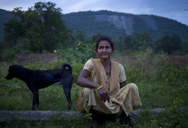 In this September 11, 2014 photo, Jema Sundi sits outside her home in barren hills where asbestos waste was dumped is visible in the background in Roro, India. An asbestos mine, abandoned nearly three decades ago still affects the people around it and 18 along with Jema were diagnosed with asbestosis in 2012. Tens of thousands more, some former mine workers, remain untested and at risk. (Photo by Saurabh Das/AP Photo)