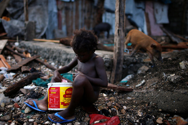 A girl takes a bath next to destroyed houses, after Hurricane Matthew hit Jeremie, Haiti, October 16, 2016. (Photo by Carlos Garcia Rawlins/Reuters)
