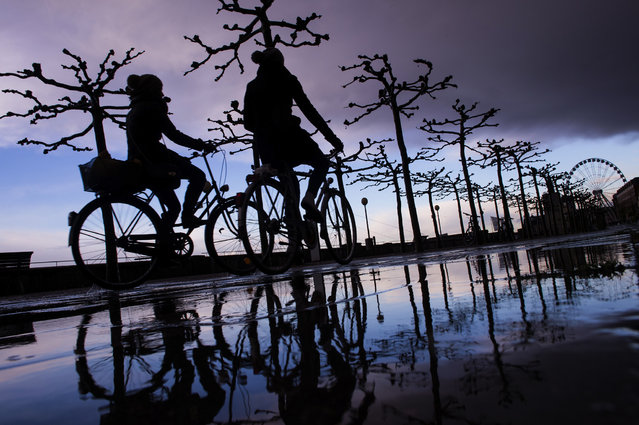 Two cyclists are reflected in a puddle shortly after a storm on the banks of the river Rhine in Duesseldorf, Germany, Thursday, December 11, 2014. (Photo by Marius Becker/AP Photo/DPA)