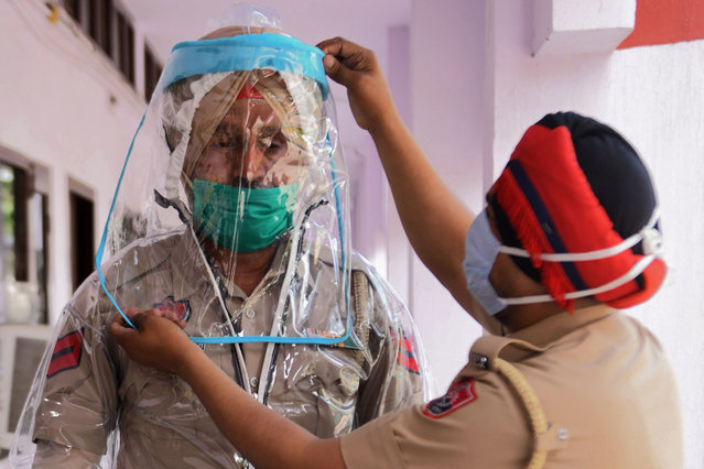 In this file photo taken on April 16, 2020 police personnel try Personal Protective Equipment (PPE) during a government-imposed nationwide lockdown as a preventive measure against the COVID-19 coronavirus, in Amritsar. (Photo by Narinder Nanu/AFP Photo)