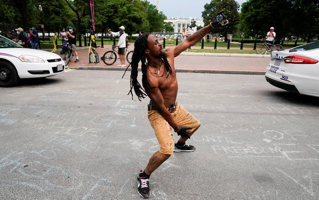 A protestor dances in the street as demonstrators face off with police at the intersection of 16th and H Street on Black Lives Matter Plaza along Lafayette Park across from the White House after Washington Metropolitan Police officers pushed back racial inequality protestors to re-open the street for the resumption of vehicle traffic in Washington, D.C., U.S., June 22, 2020. (Photo by Joshua Roberts/Reuters)