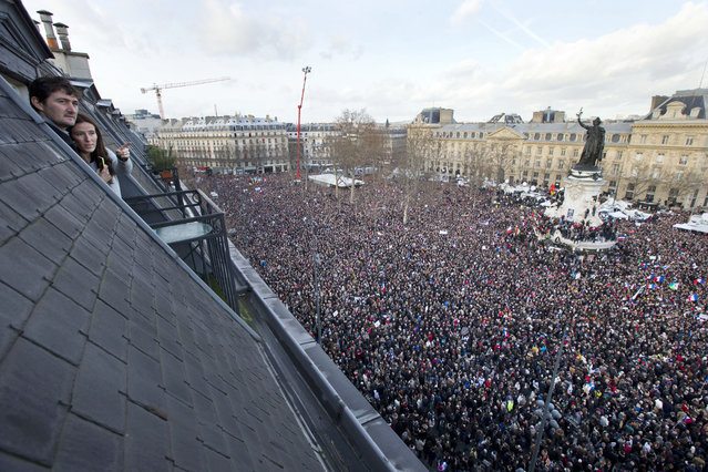 People watch from their roof-top apartment as some thousands of people gather at Republique square in Paris, France, Sunday, January 11, 2015. Thousands of people began filling France's iconic Republique plaza, and world leaders converged on Paris in a rally of defiance and sorrow on Sunday to honor the 17 victims of three days of bloodshed that left France on alert for more violence. (Photo by Peter Dejong/AP Photo)