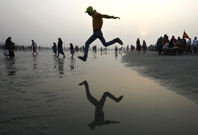 A Hindu pilgrim jumps over a water stream on a beach along the confluence of the Ganges river and the Bay of Bengal on the occasion of Makar Sankranti festival at Sagar Island, south of Kolkata January 14, 2015. Makar Sankranti is an auspicious festival celebrated by Hindus across the country that marks the start of the harvest season. (Photo by Rupak De Chowdhuri/Reuters)