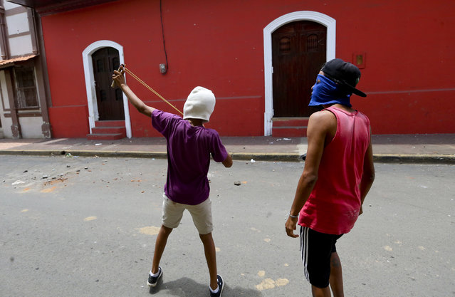 A masked protester aims his slingshot at riot police in the Monimbo neighborhood during clashes, in Masaya, Nicaragua, Saturday, June 2, 2018. More than 110 people have been killed in Nicaragua during clashes between forces loyal to President Daniel Ortega and opposition groups. (Photo by Esteban Felix/AP Photo)