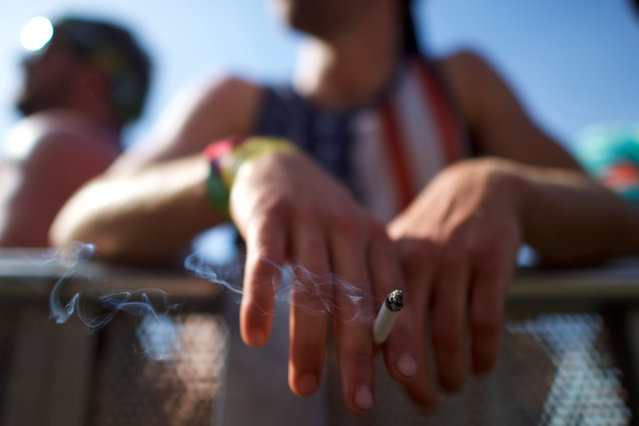 A man smokes while watching Smallpools perform on the third day of the Firefly Music Festival in Dover, Delaware U.S., June 16, 2018. (Photo by Mark Makela/Reuters)