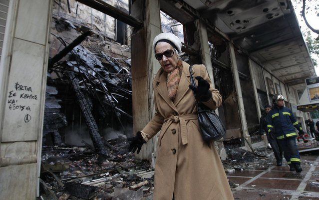 A woman picks her way past a burned-out shop after a night of violence which followed the Greek parliament approval of a deeply unpopular austerity bill in Athens, in this February 13, 2012 file photo. (Photo by John Kolesidis/Reuters)