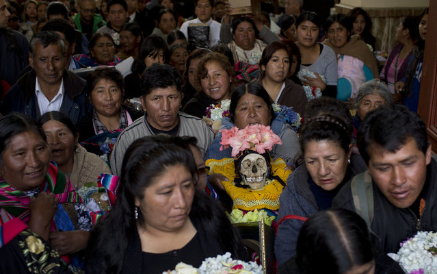 """People hold their decorated human skulls or """"natita"""", after the greeting by the priest inside the Cementerio General chapel during the Natitas Festival celebrations, in La Paz, Bolivia, Tuesday, November 8, 2016. (Photo by Juan Karita/AP Photo)"""