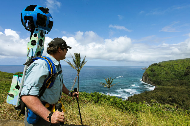 In this undated photo provided by Google, Rob Pacheco, president of Hawaii Forest & Trail, takes in the view at Pololu Valley's Awini Trail near Kapaau, Hawaii, while wearing the Street View Trekker. Hawaii's volcanoes, rainforests and beaches will soon be visible on Google Street View. The Mountain View, Calif., company said Thursday June 27, 2013  it was lending its backpack cameras to a Hawaii trail guide company to capture panoramic images of Big Island hiking trails. (Photo by AP Photo/Google)