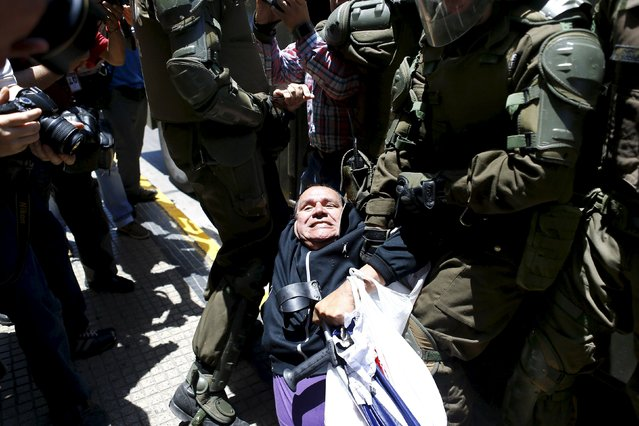 A demonstrator is detained by riot policemen during a protest against the private system of pension fund administrators in Santiago, Chile, December 10, 2015. (Photo by Ivan Alvarado/Reuters)