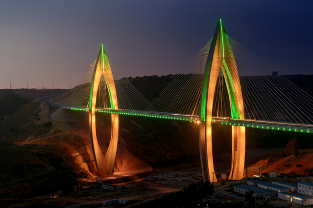 In this image released on Wednesday, July 20, 2016, the Mohammed VI Bridge illuminates the desert outside Morocco's capital city, Rabat. The recently finished bridge, which is the longest cable-stayed bridge in Africa, has been spectacularly illuminated using dynamic LED lighting by Philips Lighting. (Photo by Oussama Benbila/Philips via AP Images)