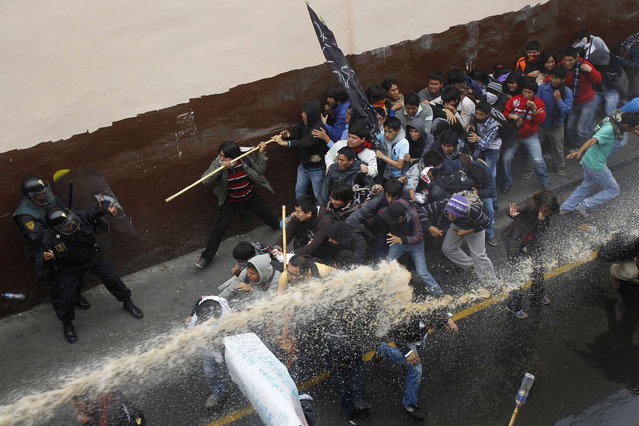 Students clash with riot police during a demonstration against the government in Lima July 4, 2013. Peruvian police fired tear gas at hundreds of students and civil servants in Lima on Thursday as they marched towards Congress to protest reforms that would impose tougher standards on universities and bureaucrats. Protesters lashed out at President Ollanta Humala for proposing the laws, which he says would improve the quality of sluggish government services and a lagging higher-education system. Critics say they would force thousands from their jobs and compromise the autonomy of Peru's universities. (Photo by Enrique Castro-Mendivil/Reuters)