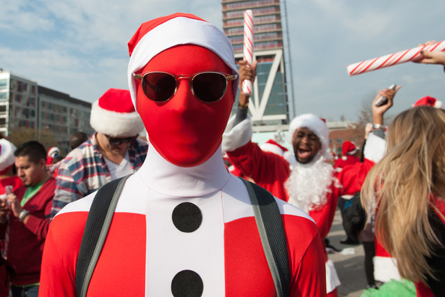 A man dressed as a Santa poses for a photo during the annual SantaCon pub crawl December 12, 2015 in the Brooklyn borough of New York City. Hundreds of revelers take part in the holiday pub crawl, though some local bars and businesses have banned participants in an effort to avoid the typically rowdy SantaCon crowds. (Photo by Stephanie Keith/Getty Images)