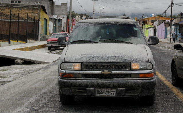 Volcanic ash coats the streets and a vehicle in San Pedro Nexapa, Mexico, Saturday, July 6, 2013. Just east of Mexico City, the Popocatepetl volcano has spit out a cloud of ash and vapor 2 miles (3 kilometers) high over several days of eruptions. Mexico's National Center for Disaster Prevention raised the volcano alert from Stage 2 Yellow to Stage 3 Yellow, the final step before a Red alert, when possible evacuations could be ordered. (Photo by Arturo Andrade/AP Photo)