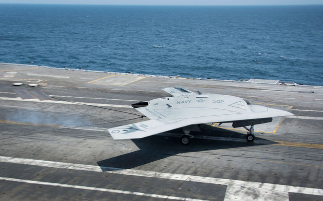 An X-47B Unmanned Combat Air System (UCAS) makes the very first carrier landing aboard the USS George H.W. Bush while afloat in the Atlantic Ocean off the coast from Norfolk, Virginia, on July 11, 2013. (Photo by Jim Watson/Getty Images)