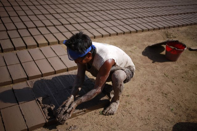 A worker settles mud in a mold to make bricks at a brick factory in Tixtla, on the outskirts of Chilpancingo, in the Guerrero state, January 26, 2015. The worker earns a salary of 15 Mexican pesos, or one dollar, for every 100 bricks made on a working day of at least 5 hours. (Photo by Jorge Dan Lopez/Reuters)