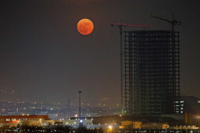 """The moon rises over Tehran in Iran, Monday, November 14, 2016. The brightest moon in almost 69 years lit up the sky, during its closest approach to earth as the """"Supermoon"""" reached its most luminescent phase. The moon won't be this close again until Nov. 25, 2035. (Photo by Ebrahim Noroozi/AP Photo)"""