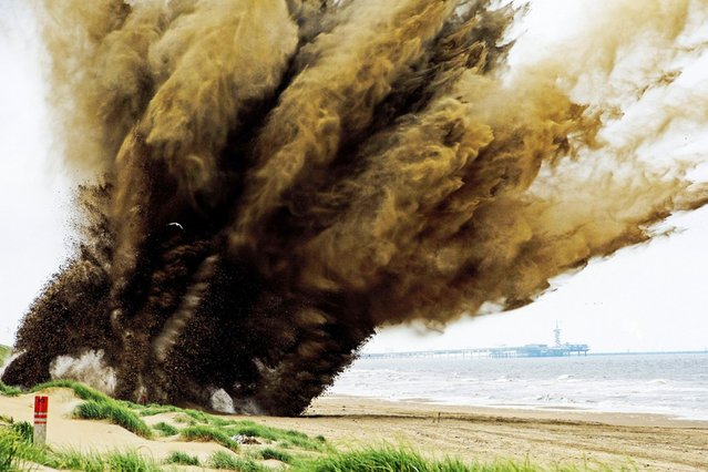 A 500-pound bomb from World War II is detonated in a controlled explosion on the beach in Wannenaar, Netherlands, on July 14, 2013. The bomb was discovered during excavation work. (Photo by Robin Utrecht/AFP Photo)