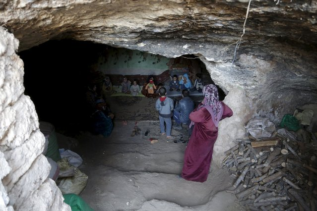 Internally displaced Syrians sit inside their makeshift shelter that is an underground cave in Om al-Seer, southern Idlib countryside, Syria December 26, 2015. (Photo by Khalil Ashawi/Reuters)