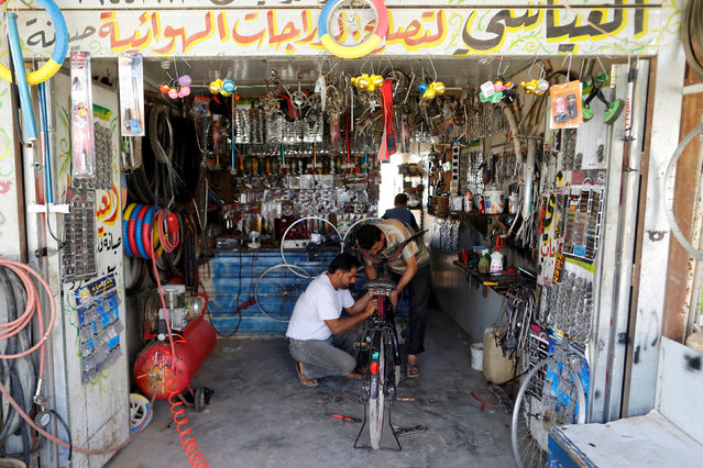 A Syrian refugee man fixes a bicycle inside his shop in Al-Zaatari refugee camp near the border with Syria, in Mafraq, Jordan October 15, 2016. (Photo by Ammar Awad/Reuters)