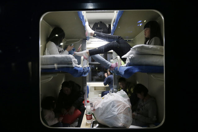 Passengers are seen through the window of a train at Beijing Railway Station, February 5, 2015. Chinese Ministry of Transport said a total of 2.807 billion trips are expected to be made during the 40-day Spring Festival travel rush, which will begin on February 4 and last until March 16, Xinhua News Agency reported. (Photo by Jason Lee/Reuters)