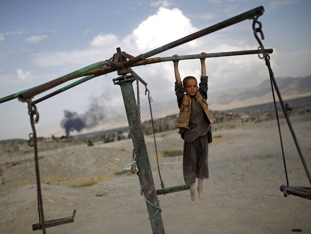 An Afghan boy plays on a merry-go-round on a hilltop in Kabul, Afghanistan July 20, 2015. (Photo by Ahmad Masood/Reuters)