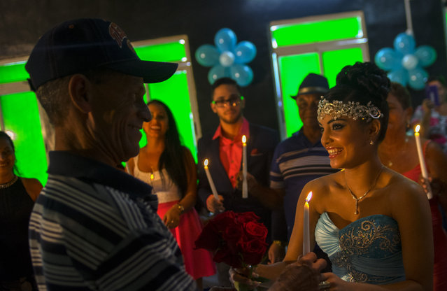 In this December 20, 2015 photo, Daniela Santos Torres, 15, gives a candle to her father as she gifts candles to the most important members of her family during her quinceanera party in the town of Punta Brava near Havana, Cuba. The quinceañera is an ancient tradition in Latin culture that marks a young girl's transition into womanhood at age 15, which means many families will go all out to give their princess a great time. (Photo by Ramon Espinosa/AP Photo)
