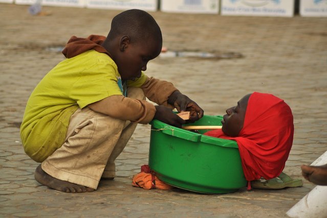 A physically challenged girl looks at her brother as she is kept in a basin to seek alms from people on the street in Kano, Nigeria December 30, 2015. (Photo by Reuters/Stringer)