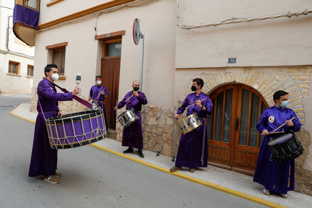 """People play drums outside their home as part of Good Friday's """"Rompida de la Hora"""" (Breaking of the hour), after annual Holy Week processions were cancelled due to the coronavirus disease (COVID-19) in Calanda, Spain, April 2, 2021. (Photo by Susana Vera/Reuters)"""