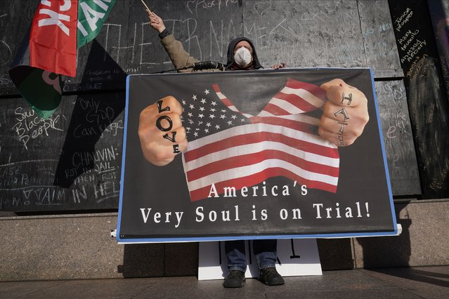A protester holds a sign across the street from the Hennepin County Government Center Tuesday, April 6, 2021, in Minneapolis where testimony continues in the trial of former Minneapolis police officer Derek Chauvin.  Chauvin is charged with murder in the death of George Floyd during an arrest last May in Minneapolis. (Photo by Jim Mone/AP Photo)